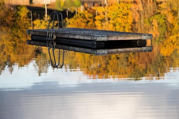 Reflectie van een houten plank en de prachtige bomen in het kalme water van een meer