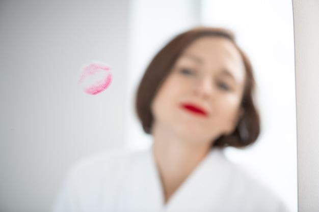 Reflectie van jonge vrouw in witte badjas staande voor spiegel met lippen print tijdens het aanbrengen van make-up