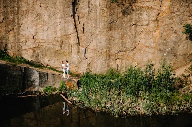 Reflectie van mensen staan ?? en knuffelen in de buurt van meer op de achtergrond van rotsen