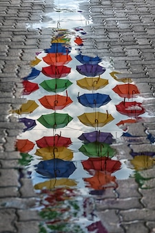 Reflectie van parasols in een plas op straat.