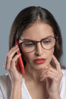 Reflecties, communicatie. nadenkend ernstige jonge vrouw in glazen met smartphone in de buurt van oor attent mediteren