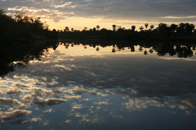 Reflecties in de rivier bij zonsondergang