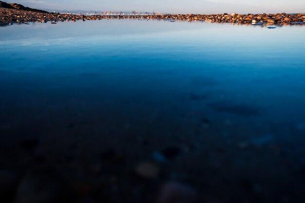 Reflecties in een plas zeewater op een strand, met de stad