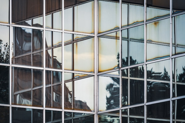 Reflecties op de hoek van de glazen gevel van een kantoorgebouw