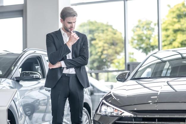 Reflecties. peinzende jonge succesvolle man in pak die de kin aanraakt en naar een nieuwe auto kijkt die in de autodealer staat