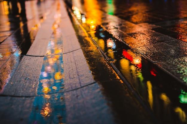 Reflecties van stadslichten op het natte wegdek.