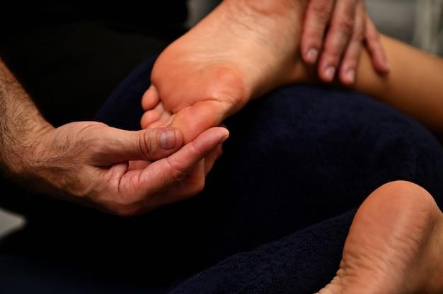 Reflexoloog die druk uitoefent op de voet met duimen. close-up van de handen van de therapeut die vrouwelijke voet masseren.