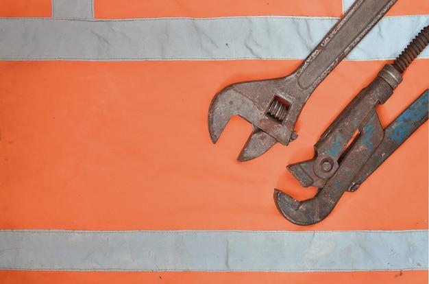 Regelbare en pijptangen tegen de achtergrond van een oranje signaalarbeidersoverhemd
