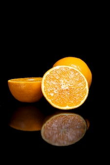 Regeling met fruit op een glanzend zwart oppervlak met zwarte achtergrond.