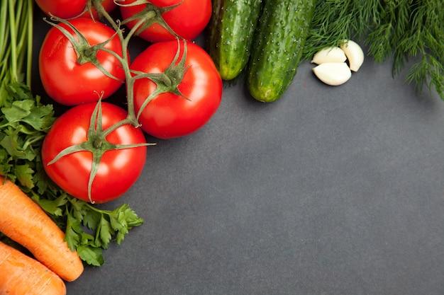 Regeling van gemengde kleurrijke groenten, geïsoleerd op donkere grijze leisteen achtergrond met lege kopie ruimte. banier