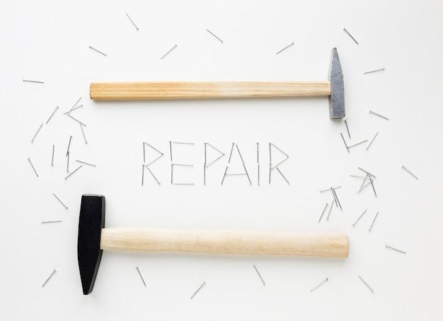 Regeling van hamers en reparatie woord geschreven met nagels