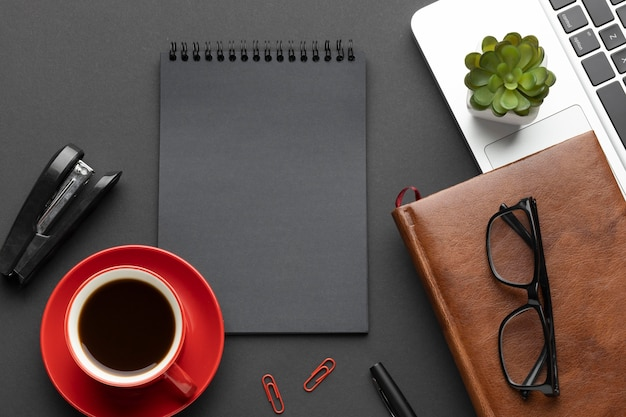 Regeling van kantoorelementen op donkere achtergrond met blocnote