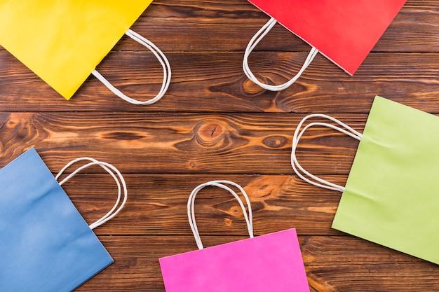 Regeling van kleurrijke papieren boodschappentas over houten achtergrond