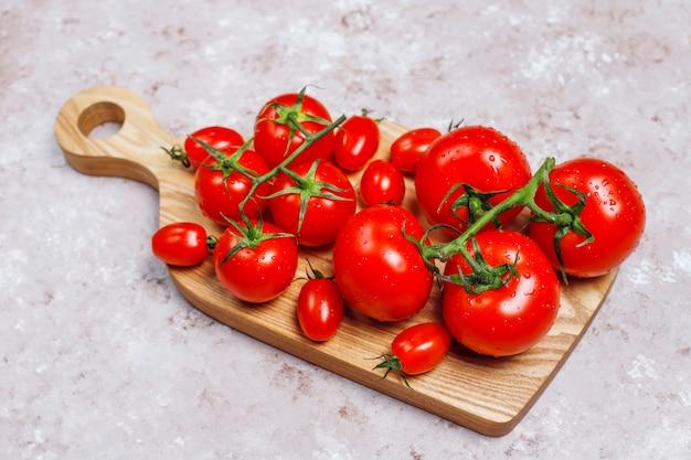 Regeling van kleurrijke verse geassorteerde tomaten op betonnen ondergrond