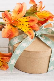 Regeling van oranje lelie bloemen en geschenkdoos