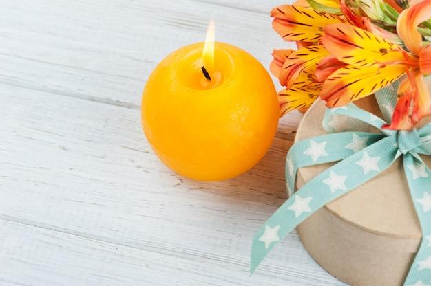 Regeling van oranje leliebloemen en kaars