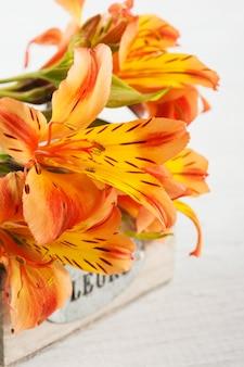 Regeling van oranje leliebloemen in houten doos