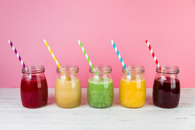 Regeling van smoothies met roze achtergrond
