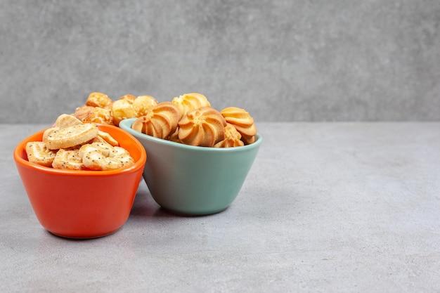 Regeling van verschillende koekjes en koekjes in kleurrijke kommen op marmeren achtergrond. Gratis Foto