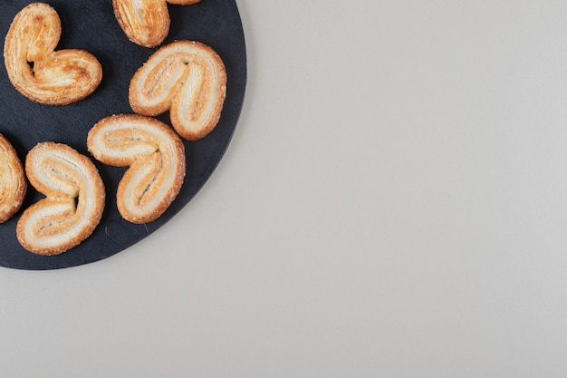 Regeling van vlokkige koekjes op een zwarte bord op witte achtergrond.