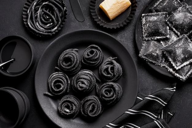Regeling van zwarte heerlijke gerechten op donkere tafel