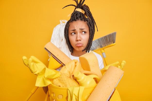 Regelmatig opruimen concept. gefrustreerde overwerkte dienstmeid spreidt handen staat verdrietig omringd door schoonmaakhulpmiddelen die bezig zijn met huishoudelijke klusjes geïsoleerd op gele achtergrond. ontevredenheid huishoudster