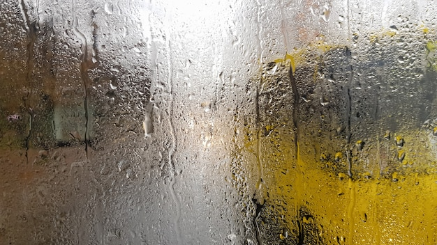 Regen op de achterruit van een auto in de herfst. binnenaanzicht van de weg met rijdende auto's in de stad door het raam van de auto met regendruppels. het besturen van een auto in het gezichtsveld van de achterruit.