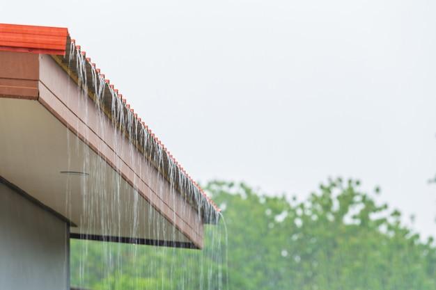 Regen stroomt naar beneden van het dak huis