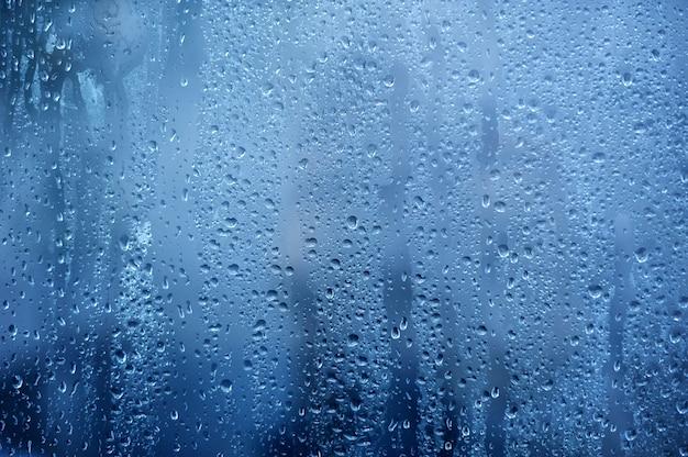 Regenachtige achtergrond, regenwater druppels op het raam of in douchecabine, herfst seizoen achtergrond