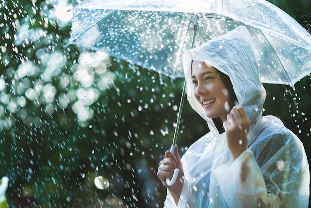 Regenachtige dag aziatische vrouw die een regenjas in openlucht draagt