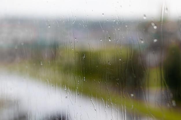 Regenachtige dag door het raam op bewolkte grijze lucht en stadsgebouwen achtergrond. concept. avond stadsgezicht achter het glazen raam met druppelende druppels water.