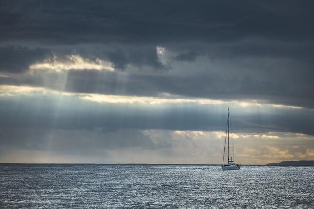 Regenachtige hemel boven het jacht in de zee. ierland.