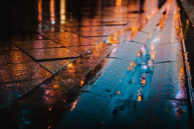 Regenachtige nacht in een grote stad, reflecties van lichten op het natte wegdek.