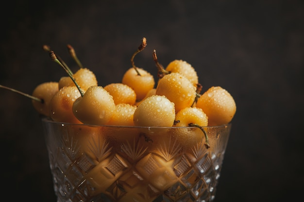 Regenachtigere kersen in een hoge fruitschaal op donkerbruin. detailopname.