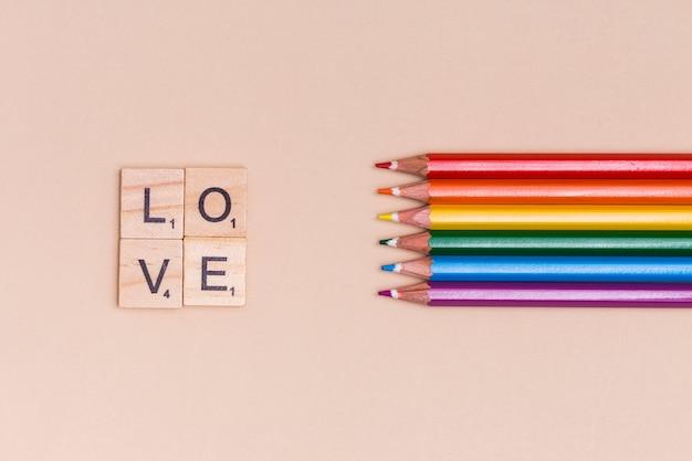 Regenboog kleurrijke potloden en liefdebrieven op beige achtergrond