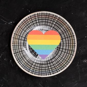 Regenboog lgbt-hart op ronde plaat op zwarte achtergrond