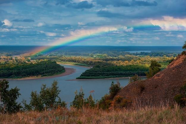 Regenboog met wolken boven een riviervallei, herfst schot