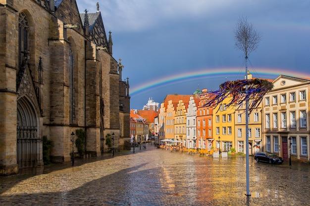 Regenboog over de kerk van st. marien en oude huizen op het marktplein in het historische centrum