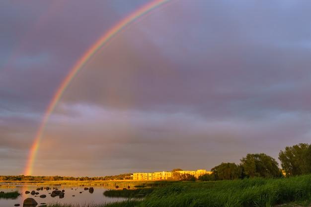Regenboog over steenachtige zeekust door zonsondergang