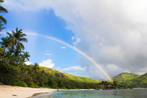 Regenboog over tropisch eiland en wit strand in seychellen