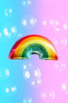 Regenboogballon op blauwe en roze achtergrond en zeepbellen. begrip lgbti. ruimte kopiëren.