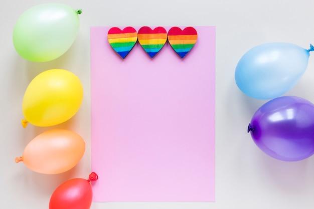 Regenboogharten met document en luchtballons