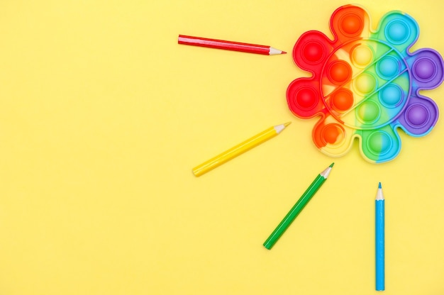 Regenboogkleur speelgoed anti-stress voor vingers pop it in de vorm van een bloem op een gele achtergrond jeugdconcept