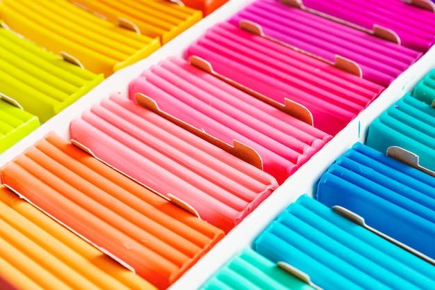 Regenboogkleuren van boetseerklei. multicolored inabox van plasticinebars, achtergrondtextuur
