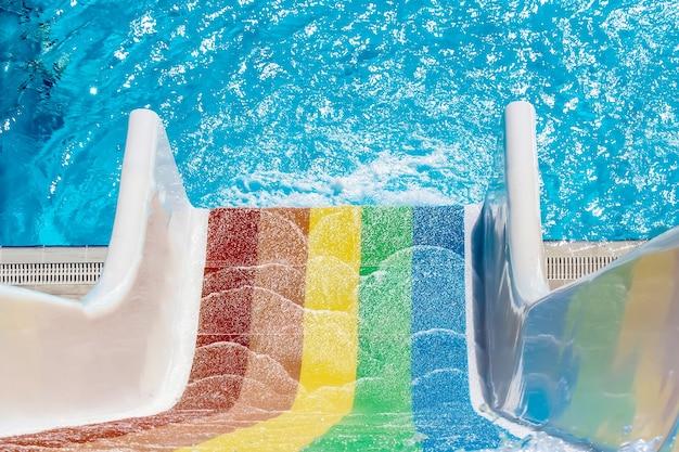 Regenboogkleurige aquaparkglijbaan bij het zwembad vi