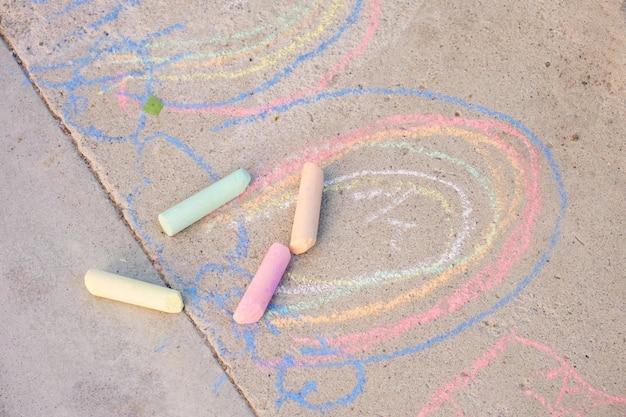 Regenboogkrijt getekend op het asfalt, symbool van de lgbt-gemeenschap, kleurpotloden op de grond kindertekening