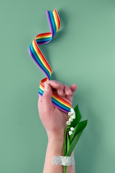Regenbooglint ter beschikking van rijpe vrouw met lelietje-van-dalenbloemen. boeket bevestigd met pleister voor medische hulp. bedankt nhs-artsen en verpleegsters!