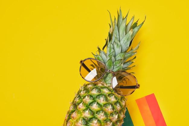 Regenboogvlag en ananas in zonnebril op gele achtergrond met kopieerruimte