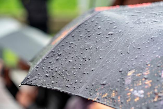 Regendag, zware regen in de stad, druppels op oppervlak van zwarte paraplu, mensen met paraplu's tijdens storm