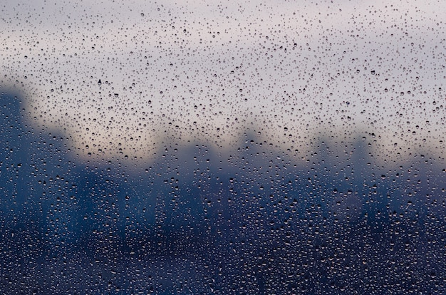 Regendaling op glasvenster in moessonseizoen met vage stadsachtergrond.
